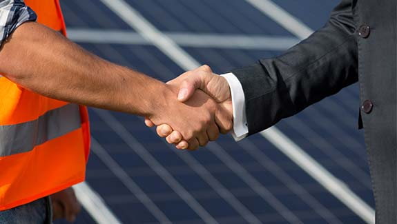 Foreman and businessman shaking hands at solar energy station. Close up view on handshake between worker and man in business suit.